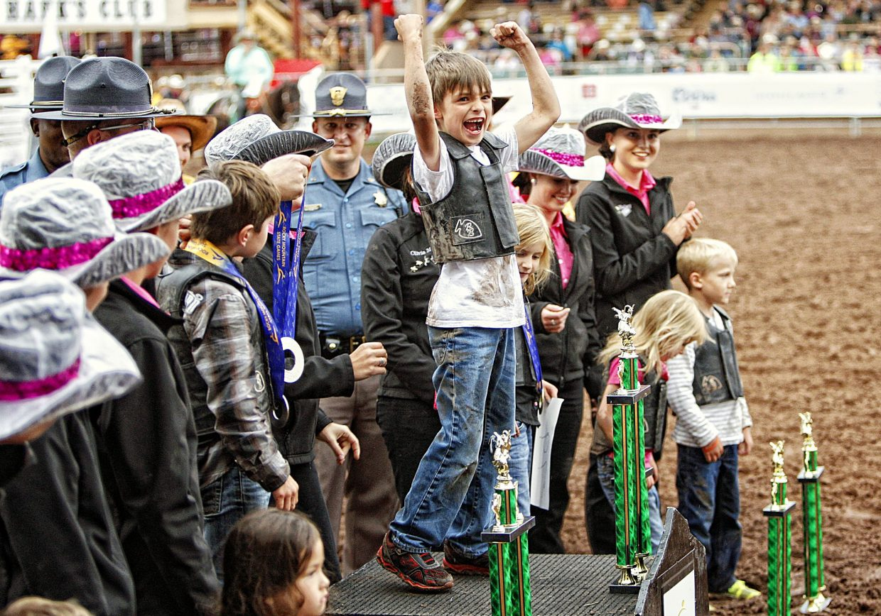 An enthusiastic Eli Diamanti of Colorado Springs, Colo., celebrates winning the mutton busting competition with raised arms and a huge smile July 13 at the 2017 Pikes Peak or Bust Rodeo