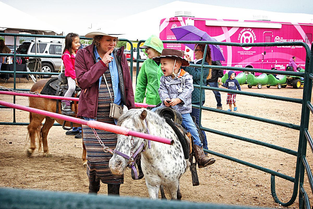 Rain or shine, youngsters of all ages had a good time at the pony ride corral located in the fan zone area of the 2017 Pikes Peak or Bust Rodeo in Colorado Springs, Colo.