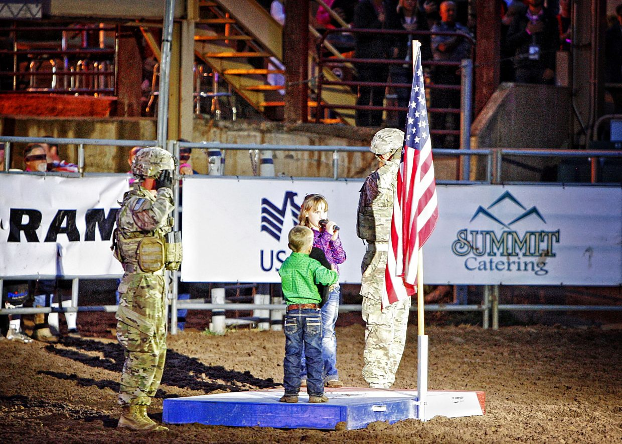 Soldiers from Fort Carson salute while Sayler Wall, 7, and her brother, Easton Wall, 4, recite the Pleadge of Allegiance at the conclusion of the rodeo on July 13. The scene was set to dsplay the patriotism of the young generation that is part of the rodeo and western community.