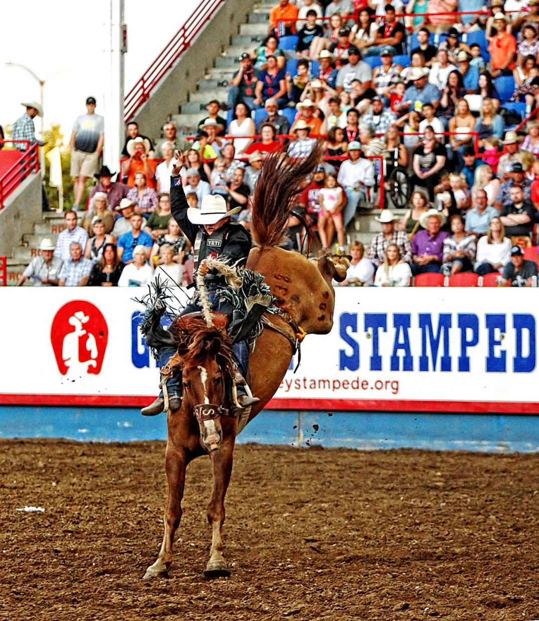 Utah saddle bronc cowboy Rusty Wright rode Ole Flame for a crowd-pleasing 87 points, which tied the Greeley Stampede's arena record and earned Wright his second consecutive saddle bronc title in two tries at the historic Colorado rodeo.