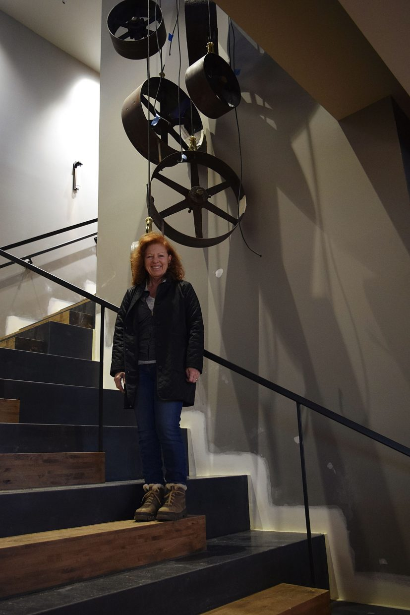 Ginger Graham stands under what will be a chandelier made of wheels from pullies the mill used. The lights were one of the many smaller details Ginger and Baker were working on Nov. 7, two days before the small open.