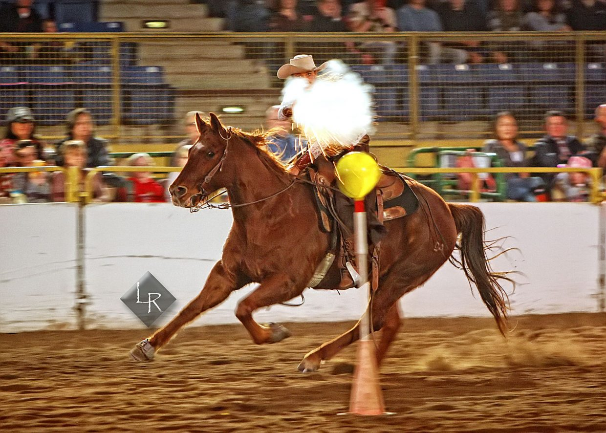 With her revolver firing, Cowboy Mounted Shooting expert Elizabeth Clavette played Annie Oakley during the Wild West Show at the 2019 National Western Stock Show. In this part of her routine, Clavette fired blank rounds at balloon targets (blank rounds will pop balloons at close range) while galloping past at speed.