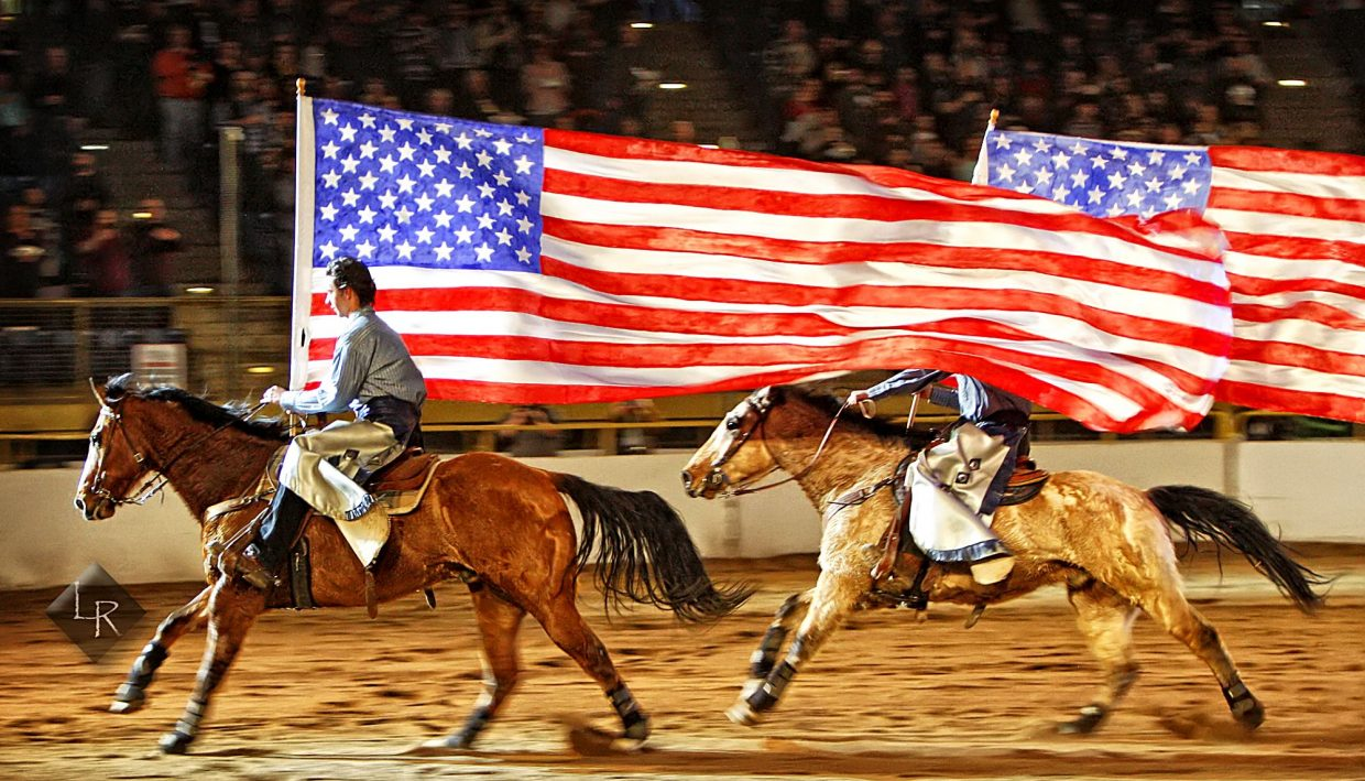 A pair of riders from the Westernaires helped kick off the action by galloping extra large versions of Old Glory around the arena at the start of the Wild West Show at the 2019 National Western Stock Show.